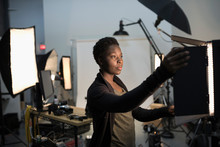 Focused Female Photographer Adjusting Lighting Equipment For Photo Shoot In Studio