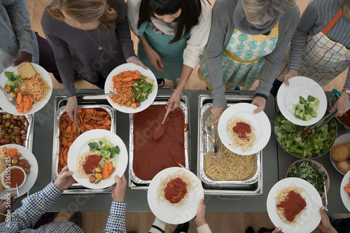 Overhead view people serving Food at soup kitchen community dinner - 316155285
