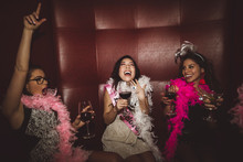 Playful, Exuberant Young Female Millennial Friends Drinking, Celebrating Bachelorette Party In Nightclub