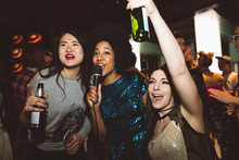 Playful Young Female Millennial Friends Drinking Beer And Singing Karaoke At Nightclub