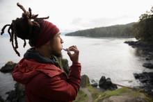 Male Backpacker Brushing Teeth On Cliff Overlooking Ocean