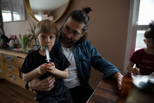 Father Giving Son Medicine At Dining Table