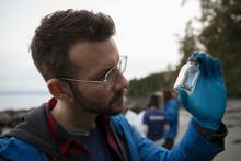 Eco-friendly Male Scientist Examining Micro Plastic Specimen On Beach