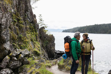 Active Senior Couple Backpacking On Cliff Overlooking Ocean
