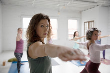 Focused Woman Practicing Yoga Warrior Two Pose In Yoga Class