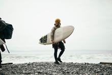 Female Surfer Carrying Surfboa...