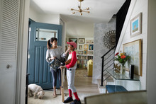 Mother Preparing To Take Tween Son To Baseball Practice In Foyer