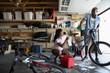 Playful couple washing bicycles in garage