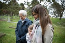 Multi-generation Women Visiting Gravesite At Cemetery