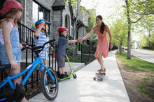 Daughter And Sons High-fiving And Cheering Mother Skateboarding On Neighborhood Sidewalk