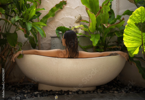 Photo Woman relaxing in outdoor bath with tropical leaves at Bali