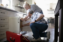Daughter With Digital Tablet Helping Senior Father Fixing Plumbing In Kitchen