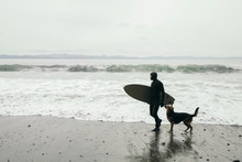 Male Surfer With Dog Carrying Surfboard On Rugged Beach