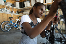 Tween Girl Fixing Bicycle In Garage