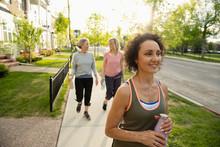 Smiling Senior Women Friends Walking, Exercising On Neighborhood Sidewalk