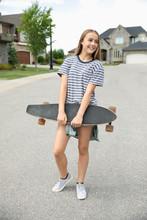 Tween Girl With Skateboard On Neighborhood Street