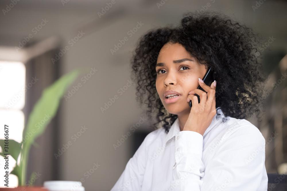 Fototapeta Pensive black woman talk over cell making decision