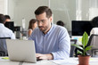 Focused male employee busy working at laptop in shared space
