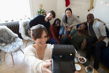 Young Woman With Instant Camera Taking Selfie With Friends In Christmas Living Room