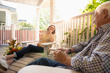 Daughter And Senior Father Relaxing On Summer Porch