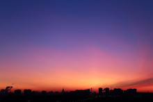 Sunrise Over The City, Scenic View. Orange Sky In Soft Colors Above Silhouettes Of High-rise Buildings, Colorful Cityscape For Background