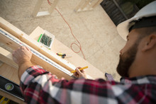 Man Measuring Wood Plank At Co...