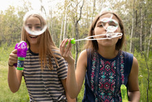 Portrait Playful Tween Girl Friends Playing With Bubble Wands