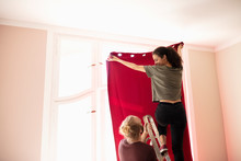 Couple On Ladder Hanging Red Curtain