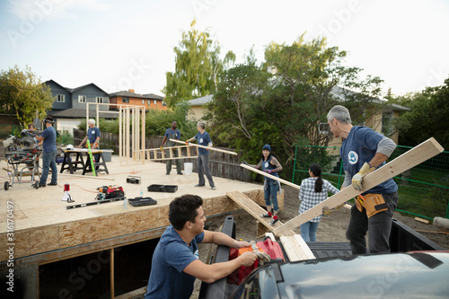 Volunteers unloading wood planks, helping build house - 316170497