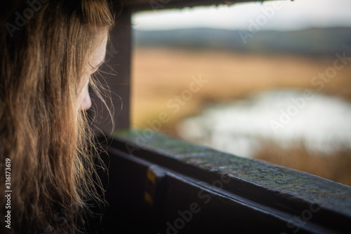 Fotografía  A Young Woman Looks Out From a Bird Hide By A Scottish Loch