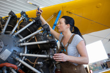 Female Engineer Inspecting And Fixing Airplane Engine