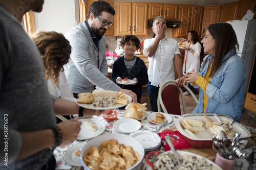 Latinx family enjoying buffet dinner in kitchen - 316176673