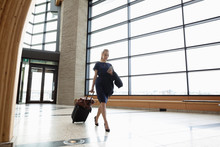 Businesswoman With Smart Phone Pulling Suitcase In Airport