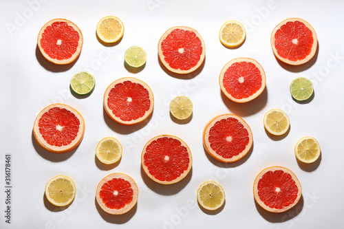 Fotografía  Flat lay composition with tasty ripe grapefruit slices on white background