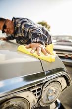 Latinx Man Waxing Vintage Car