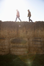 Brothers Walking On Hay Bales On Sunny Farm