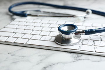 Keyboard and stethoscope on white marble table, closeup. Concept of technical support