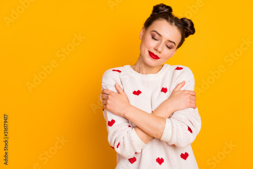 Obraz Photo of beautiful lady hugging herself shoulders eyes closed enjoy pullover softness wear hearts pattern white red knitted sweater isolated yellow color background - fototapety do salonu