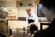 Smiling barista preparing coffee for businesswoman