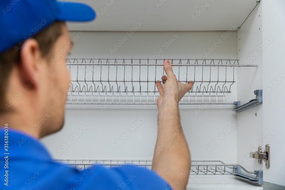 Fototapeta furniture service worker installing kitchen cabinet dish rack