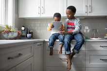 Barefoot Brothers Using Digital Tablet On Kitchen Counter