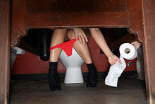 Low Section Woman With Red Thong In Nightclub Bathroom Stall