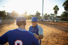 Coach Talking With Baseball Player On Sunny Field