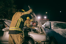 Firefighters Tending To Burnt Car Fire At Scene Of Car Accident