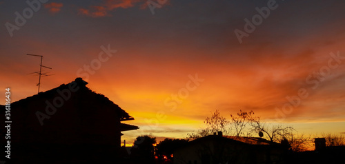 Bellissima alba tra le case e gli alberi che colora il cielo di rosso Canvas Print