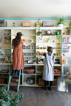 Female Business Owners Organizing Display In Apothecary Shop