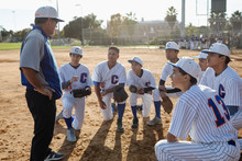 Coach And Baseball Team Huddli...