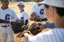 Baseball Players Joining Baseball Gloves In Huddle