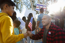 Father And Son With American Flag, Canvassing Voters