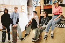 Portrait Confident Teenage Friends Hanging Out At Indoor Skate Park